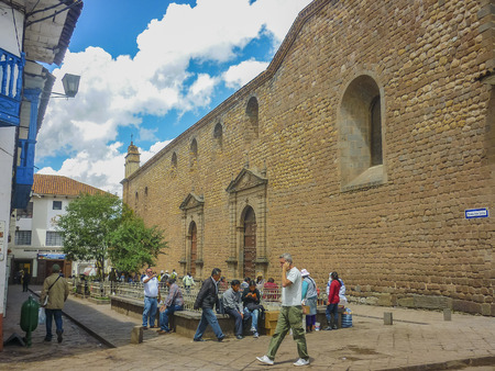 spanish style: CUSCO, PERU, APRIL 2014 - Perspective view of people walking on street with spanish style colonial houses and ancient church at background in the city of Cusco in Peru, South America. Editorial