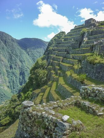 highs: Aerial view of terraces and architecture in the highs of the most famous landmark of Cuzco in Peru, the ancient inca city of Machu Picchu.