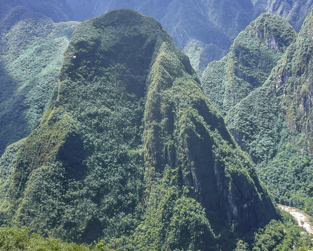 highs: Spectacular aerial view of Putucusi big mountain from the ancient inca city of Machu Picchu in Cuzco, Peru.