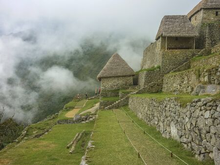 highs: Houses and terraces with fog in the air from the highs of the most famous landmark of Cuzco in Peru, the ancient inca city of Machu Picchu.