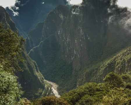 highs: Spectacular aerial view landscape of big mountains and urubamba river at distant photo taken from the highs in the ancient inca city of Machu Picchu in Cuzco, Peru.