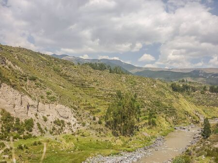 outsides: Beautfiul landscape view of a river surrounded by moutains andes range a sunny day at Colca valley in the outsides of Arequipa city in Peru, South America. Stock Photo