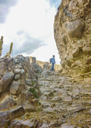 explorer man: Adult explorer man peering the rocks in Colca valley in the outsides of Arequipa city in Peru, South America. Stock Photo