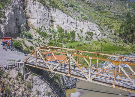 outsides: High angle view of rusty bridge surrounded by moutains andes range at a sunny day at Colca valley in the outsides of Arequipa city in Peru, South America. Stock Photo