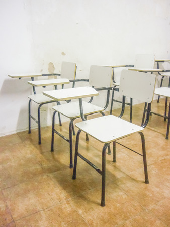 Perspective view of a bunch of empty classroom white chairs. photo