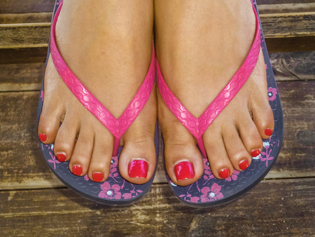 toenails: Young woman foot with decorative sandals and red toenails in wooden floor closeup photo.