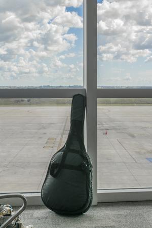 guitar case: Caja de la guitarra Negro apoy� en la ventana con la pista de aterrizaje vac�a y cielo con nubes en el fondo.
