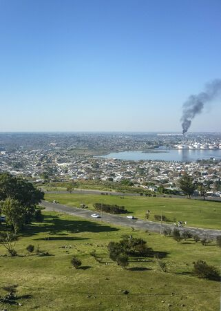 artigas: Aerial view of west coast of Montevideo from Fortaleza General Artigas with a big cloud of smoke from the oil refinery as the main subject. Stock Photo