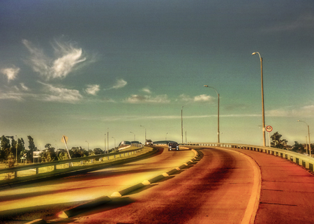 edited photo: Color edited urban view of bridge in the city of Montevideo in Uruguay in a nice day with clouds and sky at background.