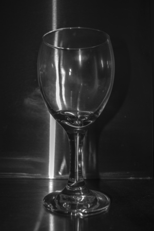 stell: High contrast style photo of empty glass of wine against stained stell background. Stock Photo