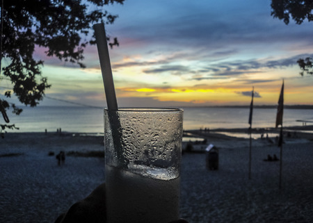 Beautiful aerial view of sunset at the beach with a hand holding a drink as the main subject and shore and sky at background. photo