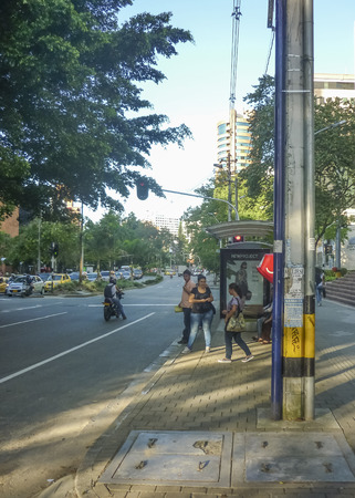 medellin: MEDELLIN, COLOMBIA, DECEMBER - 2014 - People at stop bus in El Poblado neighbourhood, one of the most exclusive places in Medellin, Colombia.