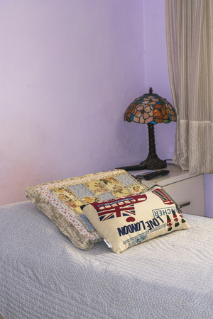 bedcover: Peaceful interior bedroom scene with tiffany stlye lamp and british style pillow and orante woven blanket homemade home decor.