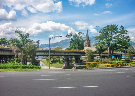 medellin: Inside car view of empty highway with bridge and mountains at background in Medellin, one of the most important cities of Colombia.