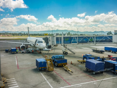 provision: MEDELLIN, COLOMBIA, DECEMBER 30 - 2014 - Perspective view of plane parked at airport receiving provision in Medellin airport in Colombia.