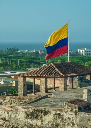 colombian flag: Nice view of the coast and colombian flag from San Felipe de Barajas Fortress, an spanish colonial style defense building located in Cartagena,  Colombia