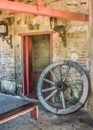 barajas: Door, antique lamps and wood wheel carriage in San Felipe de Barajas Fortress, an spanish colonial style defense building located in Cartagena,  Colombia