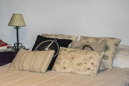 home made: Interior bedroom scene with lamp and home made designed pillow in bed. Stock Photo