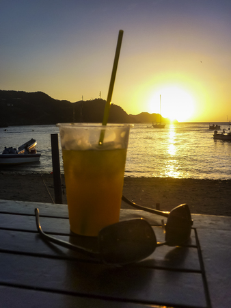 caribbean drink: TAGANGA, COLOMBIA, JANUARY - 2015 - Drink and glasses on the table at sunset scene at caribbean bay called Taganga, one of the most important watering places in Colombia