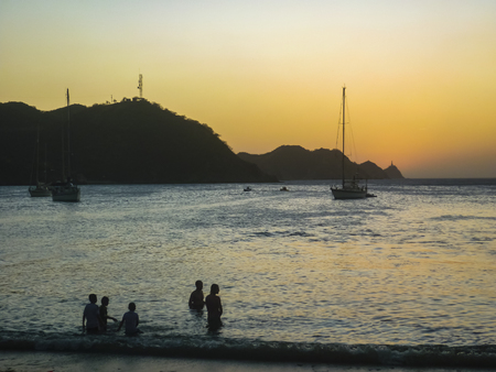 important people: TAGANGA, COLOMBIA, JANUARY - 2015 - Sunset scene with boats and people silhouettes at caribbean bay called Taganga, one of the most important watering places in Colombia