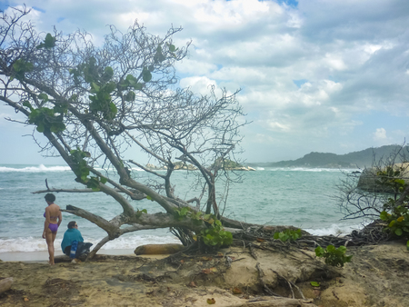 famous women: MAGDALENA, COLOMBIA, JANUARY - 2015 - Two women at wild coast at Cabo San Juan, the most famous beach of tayrona park, a touristic protected area in the colombian northern caribbean region.