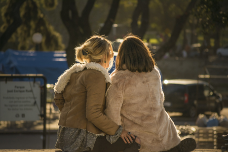 lesbian love: Back view of two adult couple or friends women sitting at park in Montevideo Uruguay.