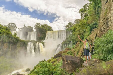 man waterfalls: PORT IGUAZU, ARGENTINA, MARCH - 2015 - Young man taking a selfie with spectacular view of one of the waterfalls at Iguazu park in the background