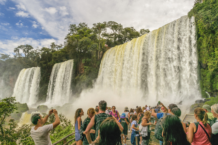 PORT IGUAZU, ARGENTINA, MARCH - 2015 - Tourists enjoying an spectacular view of one of the waterfalls at Iguazu park in the argentinian border.