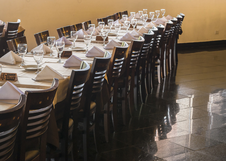 costumers: Perspective view of empty restaurant with big table and chairs ready to receive costumers. Stock Photo