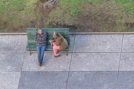 sidewalk talk: MONTEVIDEO, URUGUAY, AUGUST - 2015 - High angle view of a adult couple sitting on chair at the independence square in Montevideo, the capital of Uruguay.