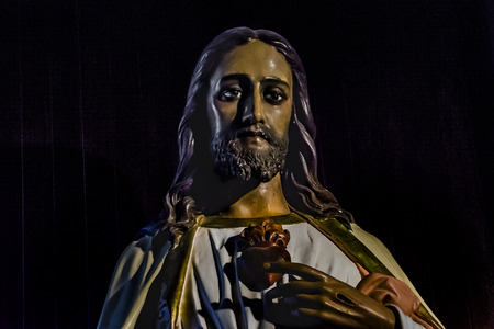 edited photo: Low angle view of chest and face of jesus christ wood sculpture isolated against black background Stock Photo