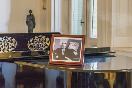 ocampo: BUENOS AIRES, ARGENTINA, AUGUST - 2015 - Living room interior view of grand piano and portrait of Igor Stravinsky in Villa Ocampo, the home of the famous argentinian intellectual Victoria Ocampo.