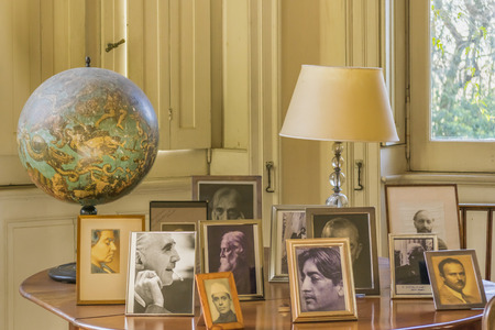 BUENOS AIRES, ARGENTINA, AUGUST - 2015 - Living room interior view of a bunch of portrait frames personalities of the 20th century in Villa Ocampo, the home of the famous argentinian intellectual Victoria Ocampo. Editorial