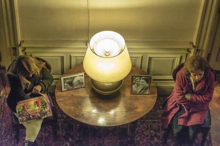 ocampo: BUENOS AIRES, ARGENTINA, AUGUST - 2015 - Top view of two mature women sitting on chairs at interior living room with a lamp on desk separating each other