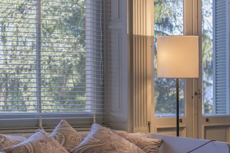 ocampo: Peaceful interior room scene with pillows and blinds showing blue sky and trees at Villa Ocampo, the home of the famous argentinian intellectual Victoria Ocampo. Stock Photo