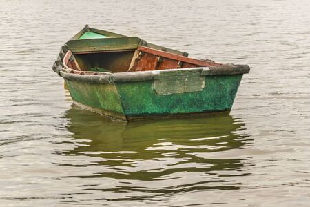 Old small fishing boat resting in the waters of Santa Lucia river in the outside of Montevideo in Uruguay. Stock Photo