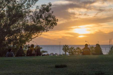 MONTEVIDEO, URUGUAY, OKTOBER - 2015 - junge Leute, die den Sonnenuntergang von der Spitze des Hügels in einem Park vor Fluss in Montevideo, Uruguay aufpassen Editorial
