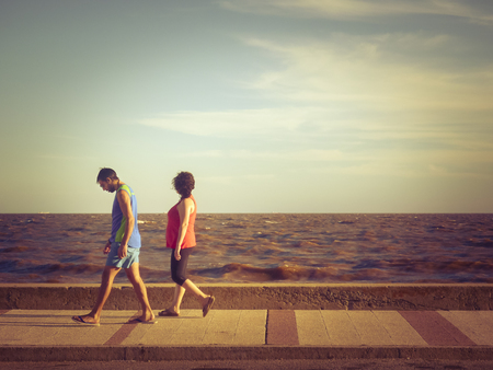 edited photo: MONTEVIDEO, URUGUAY, JANUARY - 2016 - Color edited photo of adult couple walking at summer time on the boardwalk with the river and blue sky at background in the coast of Montevideo, Uruguay.