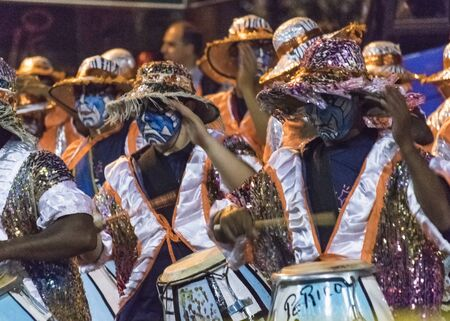 costumed: MONTEVIDEO, URUGUAY, JANUARY - 2016 - Costumed men drummers playing traditional music called candombe at the inagural parade of carnival of Montevideo, Uruguay