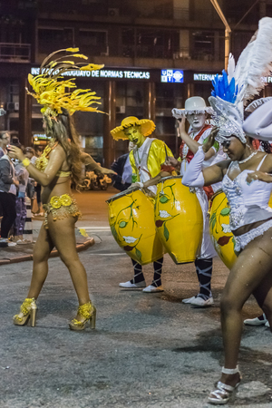 costumed: MONTEVIDEO, URUGUAY, JANUARY - 2016 - Attractive costumed women dancers and candombe drummers at inaugural parade of carnival of Montevideo, Uruguay