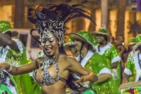 costumed: MONTEVIDEO, URUGUAY, JANUARY - 2016 - Attractive costumed young black woman dancing and candombe drummers at inagural parade of carnival of Montevideo, Uruguay Editorial
