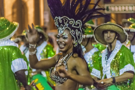 montevideo: MONTEVIDEO, URUGUAY, JANUARY - 2016 - Attractive costumed young black woman dancing and candombe drummers at inagural parade of carnival of Montevideo, Uruguay Editorial