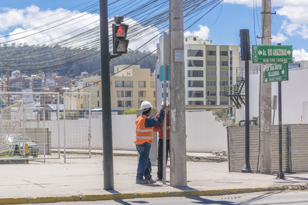 outskirts: QUITO, ECUADOR, OCTOBER - 2015 - Urban scene of two construction workers talking in outskirts district of Quito city, the capital of Ecuador in South America