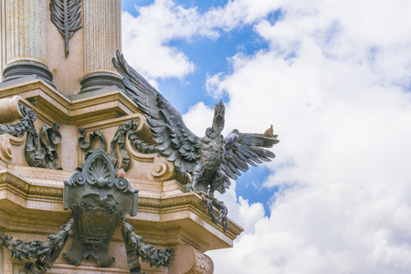 neo classical: Low angle view of detail of independence monument with neo classical style column and ornate sculptures at the historic center of Quito in Ecuador.