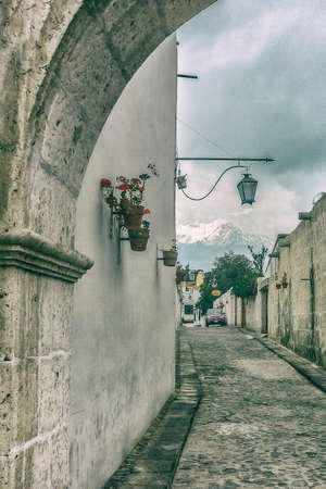 edited photo: Digital color edited photo showing a colonial street with snow mountain and dramatic cloudy sky at background in the historic center of Arequipa in Peru Stock Photo