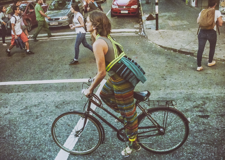 edited photo: MONTEVIDEO, URUGUAY, MARCH - 2016 - Urban scene photo of attractive young woman riding a bicycle in 18 de Julio street, the main avenue of the center of Montevideo, Uruguay.