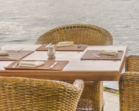 pablo: Wicker chairs an wood table with forks and tablecloths with water at background in San Pablo lake, Imbabura, Ecuador Stock Photo