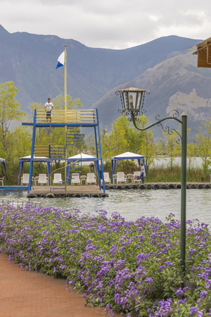 pablo: IMBABURA, ECUADOR - OCTOBER - 2015 - Detail view of touristic location with nice garden and chairs in front of San Pablo lake and big mountains at background in Imbabura, Ecuador Stock Photo