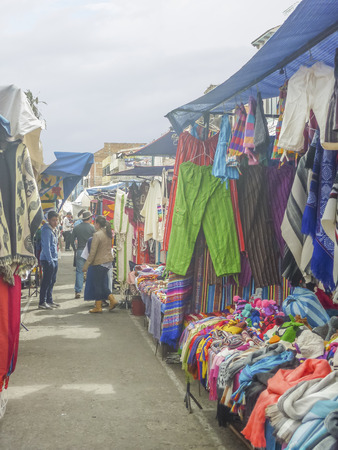 cheaper: OTAVALO, ECUADOR, OCTOBER - 2015 - Traditional indigenous clothing at street market in Otavalo, a famous city for his cheaper and quality on typical textiles Editorial