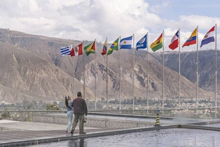 international flags: Couple watching south american flags waving at Unasur building, an international organization of south american countries located in the famous middle earth line in Ecuador